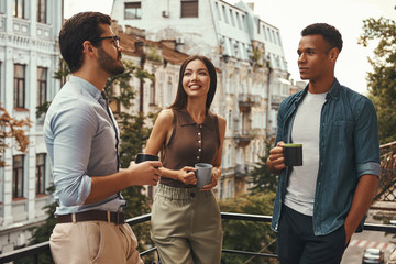 Coffee break. Young cheerful colleagues in casual wear holding cups and talking with each other while standing on the office balcony