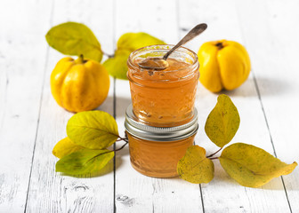 Homemade quince jam in glass jars and fresh quince with leaves. Selective focus. Copy space. Wall mural