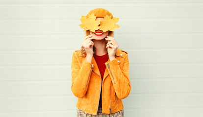 Autumn mood! happy smiling woman holding in her hands yellow maple leaves hiding her eyes over gray wall background Wall mural