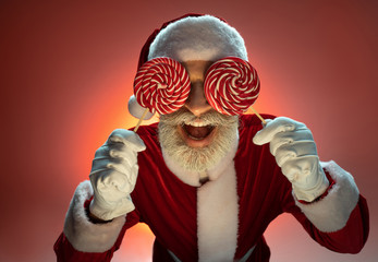 Elderly Santa Claus holding lollipops near face