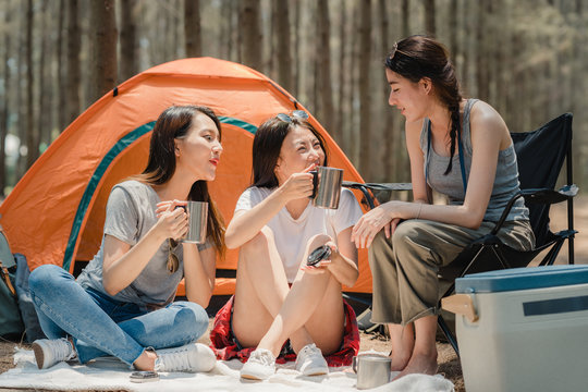 Group of young Asian friends camping or picnic together in forest, teenager female enjoy moment talking in front of their tent. Women do adventure activity and travel on holidays vacation in summer.