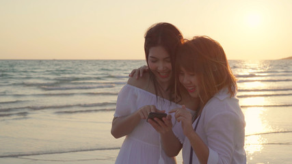 Young Asian lesbian couple using smart phone near beach. Beautiful women lgbt couple happy relax enjoy love moment when sunset in evening. Lifestyle lesbian couple travel on beach concept