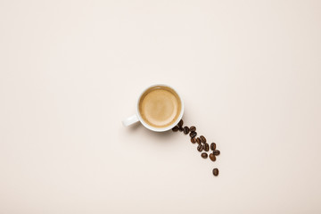 top view of cup with tasty coffee near coffee grains on beige background