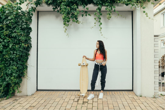 Fashionable girl in street clothes stands background of white garage door with longboard in her hands and looks away.Stylish hispanic girl posing with skateboard on white wall background with ivy