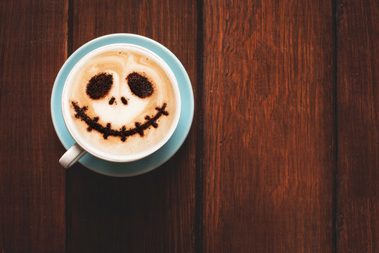 Cup of coffee with scary Jack's face. Halloween background. Halloween party.