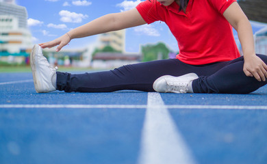 Young woman stretching her legs before running and exercising on running track. Young woman warming up outdoors. Sport and exercise concept.