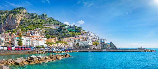 Panorama of Amalfi on hills leading down to coast, comfortable beaches and azure sea on Amalfi Coast in Campania, Italy