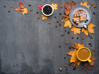 Wall Mural - Seasonal autumn background. Frame of colorful maple leaves and a cup of hot drink, coffee, latte or cappuccino, nutmeg, cake, black currant and cinnamon over grey.