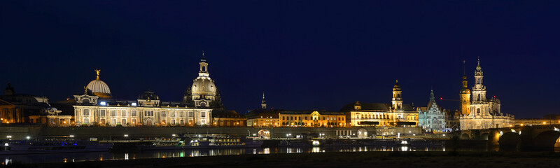 Night panorama - Elbe river embankment and Dresden Cathedral of the Holy Trinity or Hofkirche and Dresden Castle, Saxony, Germany