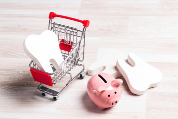 Pink piggy bank with teeth in shopping trolle on a light wooden background.