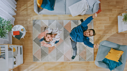 Young Happy Couple is Energetically Dancing and Jumping in an Apartment. Cozy Living Room with Modern Interior with Carpet, Sofa, Chair, Coffe Table, Book Shelf, Plant and Wooden Floor. Top Down.