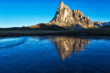 Mount Passo Gyau reflected in the frozen lake, Dolomites, Italy