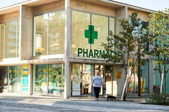 STRASBOURG, FRANCE - AUG 21, 2015: Adult woman with dog walking toward pharmacie