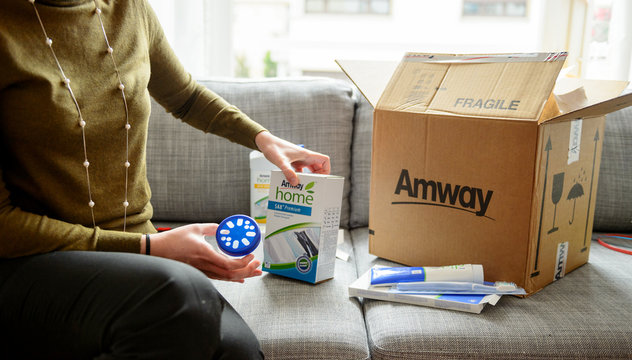 PARIS, FRANCE - OCT 20, 2015: Woman unpacking unboxing cardboard carton box with protective foam pads inside after buying ordering online via internet Multi-level marketing products from Amway