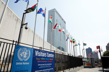 New York, New York, USA - August 18, 2011: The United Nations building on the east side of Manhattan. Visitors Centre sign and international flags in the foreground.