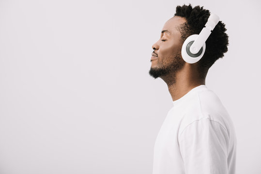 side view of happy african american man listening music in headphones on white