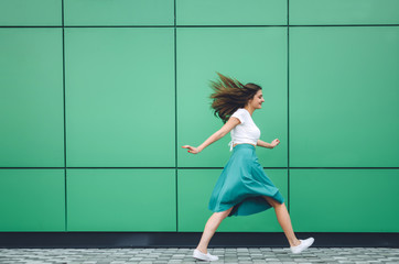 Young women dressed in white topic and turquoise skirt with coral bag jumping near grey street backgraund. Fashion and stylish concept. Wall mural