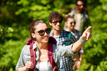 travel, tourism, hike and people concept - woman showing something to group of friends walking with backpacks in forest Wall mural