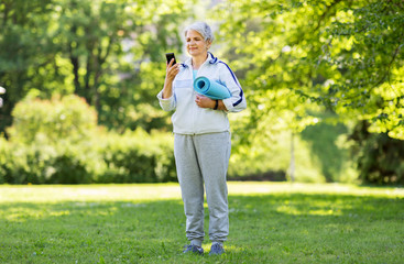 fitness, sport and healthy lifestyle concept - happy smiling senior woman with exercise mat and smartphone at park