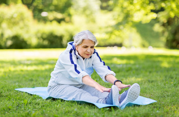 fitness, sport and healthy lifestyle concept - happy smiling senior woman exercising on mat at summer park