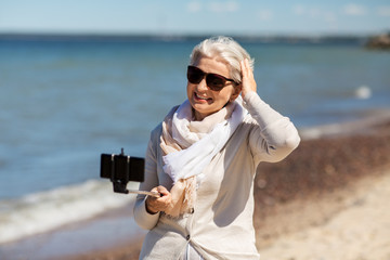 old people and leisure concept - happy smiling senior woman taking picture by smartphone and selfie stick on beach in estonia