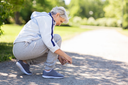 fitness, sport and healthy lifestyle concept - senior woman tying shoe laces at summer park