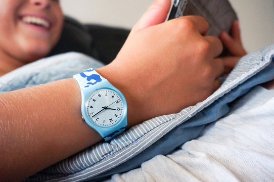 Blue Swatch watch on teenager's hand