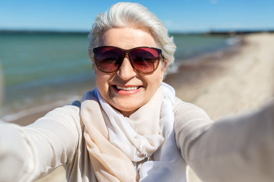 old people and leisure concept - happy smiling senior woman in sunglasses taking selfie on beach in estonia