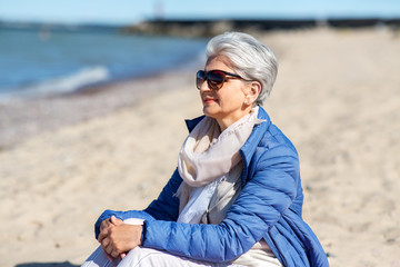 people and leisure concept - happy senior woman in sunglasses and jacket on beach in estonia