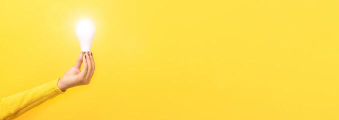 Wall Mural - idea solar energy, hand holding light bulb, illuminated light bulb, panoramic mock up over yellow background