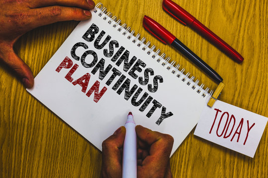 Writing note showing Business Continuity Plan. Business photo showcasing creating systems prevention deal potential threats Man holding marker notebook clothepin reminder wooden table cup coffee