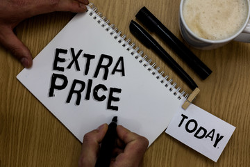 Writing note showing Extra Price. Business photo showcasing extra price definition beyond the ordinary large degree Man holding marker notebook clothepin reminder wooden table cup coffee