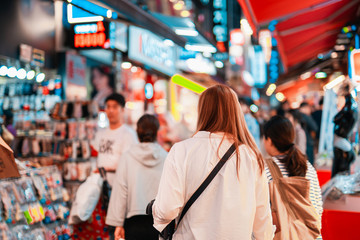 local travel activity concept from asian woman shopping and eat street food at night of south korea market Fotomurales