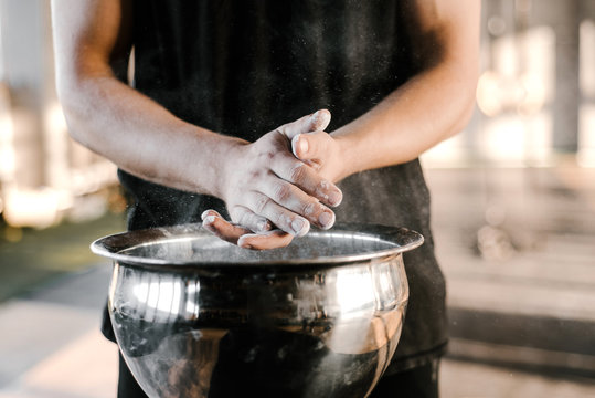 Crop man coating hands with talc