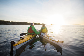 Two people kayaking in the sunshine.