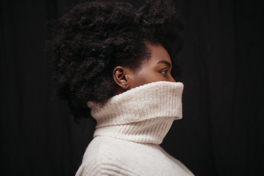 Portrait of woman with lower face covered in turtleneck shirt