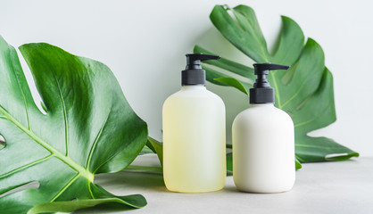 Cosmetic set of two blank label bottles for mockup packaging of skincare product cream, shampoo, conditioner on grey background with green leaves. Natural beauty product concept.