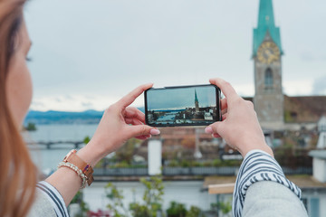 Young woman taking smartphone picture in the city, Zurich, Switzerland