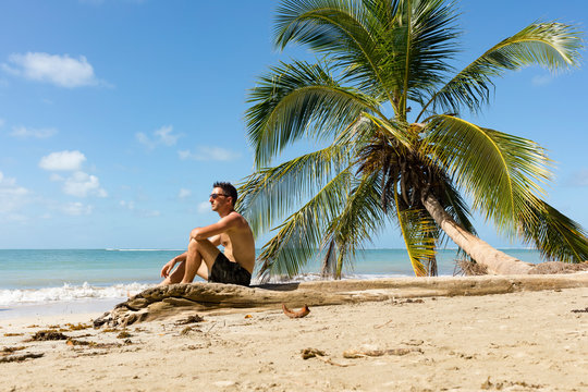 Man sitting on a tropical beach, Cahuita National Park, Costa Rica