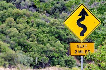 Yellow road sign indicating Winding Road ahead.