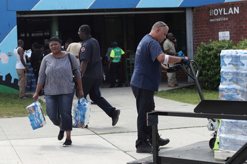 Woman carries cases of bottled water distributed for free from a recreation center as residents in some parts of the city continue to face a water crisis after high levels of lead were found in their drinking water in Newark, New Jersey