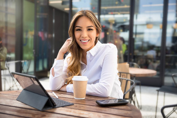 Portrait of a beautiful mixed ethnicity latin female student entrepreneur, working from laptop at coffee shop Wall mural