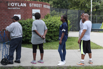 People wait in line for cases of bottled water distributed for free from a recreation center as residents in some parts of the city continue to face a water crisis after high levels of lead were found in their drinking water in Newark, New Jersey