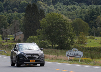 A car passes a sign for Bethel, New York near the original site of the Woodstock Festival on its 50th anniversary in Bethel, New York