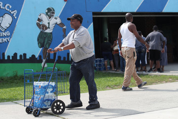 Man pushes cases of bottled water distributed for free from a recreation center as residents in some parts of the city continue to face a water crisis after high levels of lead were found in their drinking water in Newark, New Jersey