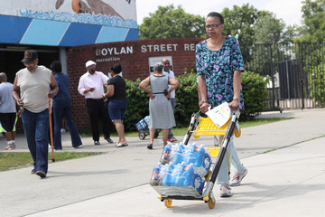Woman pushes cases of bottled water distributed for free from a recreation center as residents in some parts of the city continue to face a water crisis after high levels of lead were found in their drinking water in Newark, New Jersey