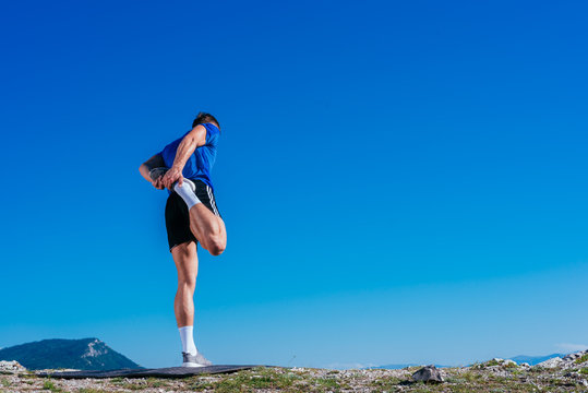 Blonde athlete wearing blue dry-fit shirt stretching and preparing for a workout while standing on top of a cliff which has an amazing view.