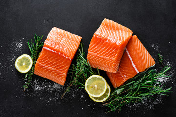 Salmon. Fresh raw salmon fish fillet with cooking ingredients, herbs and lemon on black background,...