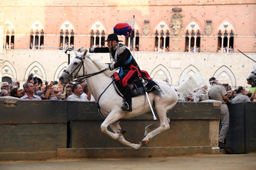 Mounted Italian Carabinieri police charge around the track with swords drawn prior to a training session of the historical Palio of Siena horse race in Siena