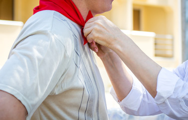 Woman ties red silk neckerchief to a man